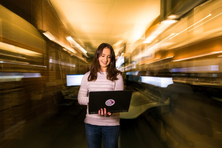 Seattle tech female employee smiling while working on laptop at office