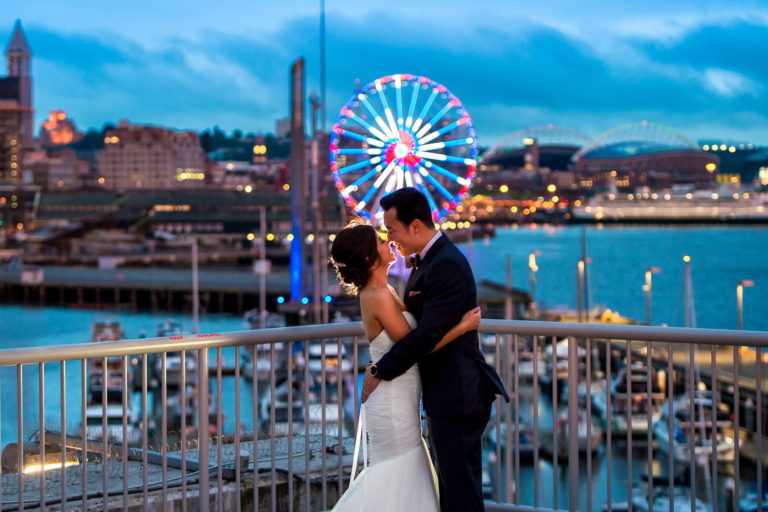 Bride and groom looking at each other on top of Bell Harbor Conference Center overlooking Seattle waterfront during sunset