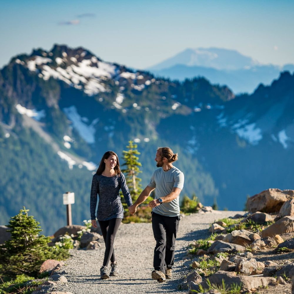 Couple holding hands walking on a trail at mt. rainier with mountains in the background