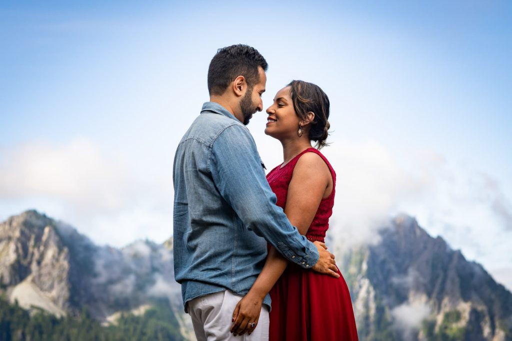 Couple with their arms around each other facing each other with mountains in background