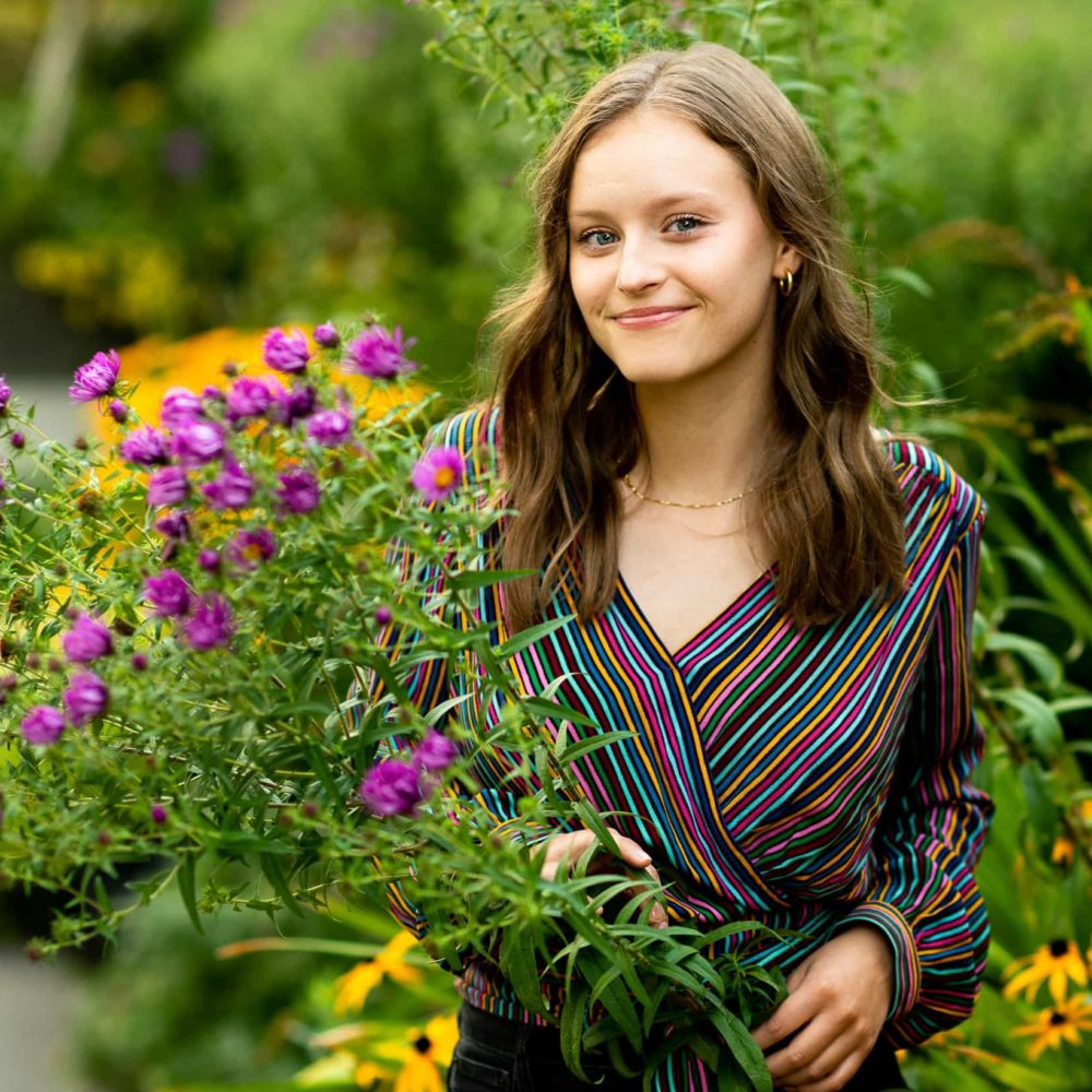 Girl smiling next to colorful plants at the Ballard Locks in Seattle for her senior photos