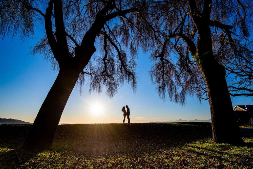 Couple facing each other silhouetted at a park in Seattle