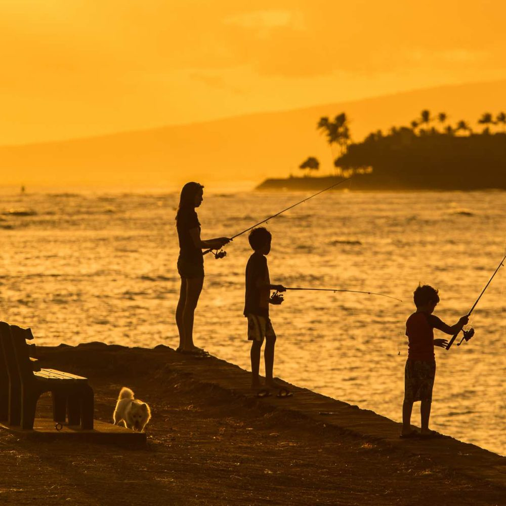 Fishing at a park in Oahu, Hawaii at sunset