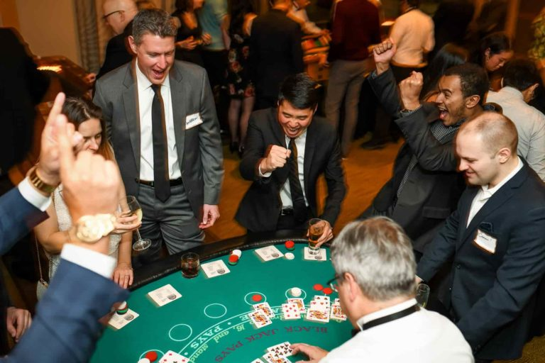Employees having fun at a poker table at Four Seasons during their annual corporate party.