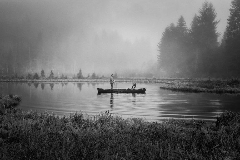 Man rowing canoe standing up while his fiancee sits