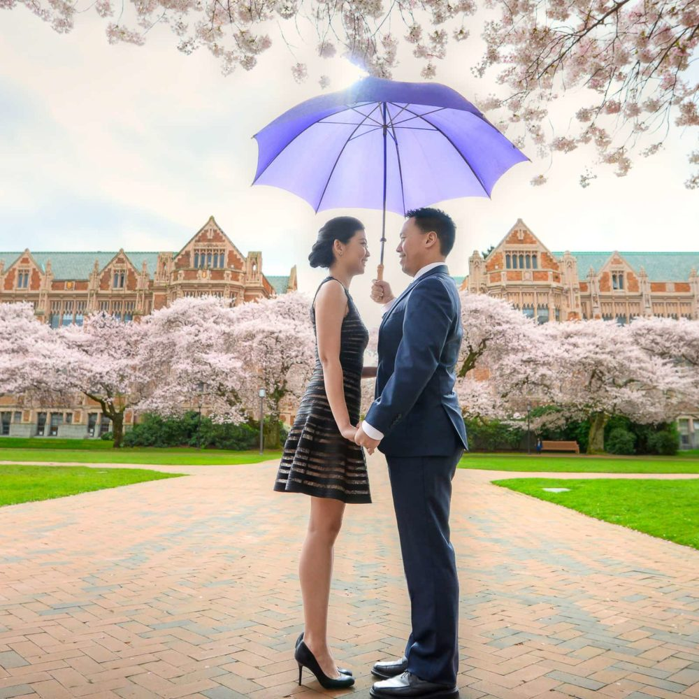 Couple at University of Washington holding umbrella while looking at each other